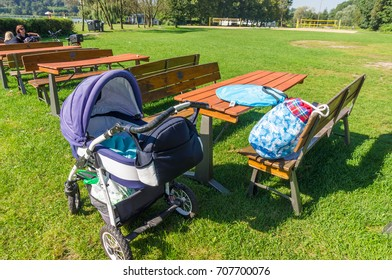 Baby buggy standing next to a wooden table and benches on green grass at a park on August 2017 in Poznan, Poland