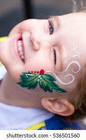 Baby caucasian girl toddler in profile with colorful christmas face painting beaming in joy