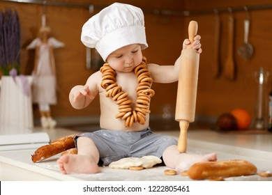 Baby chef with wooden rolling pin and cook hat in the kitchen.