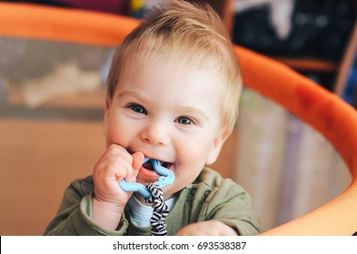 Baby chewing on teething ring toy. first teeth.
