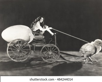 Baby chick pulling cart with woman and giant egg