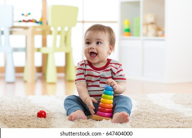 Baby child playing with educational pyramid toys at home. Little kid boy have fun indoors