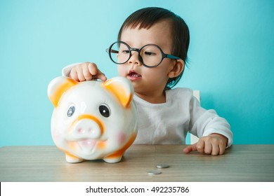 Baby child putting a coin into a piggy bank, kid saving money for future concept