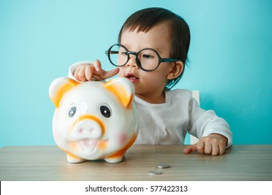 Baby child putting a coin into a piggy bank the kid saving money for future concept
