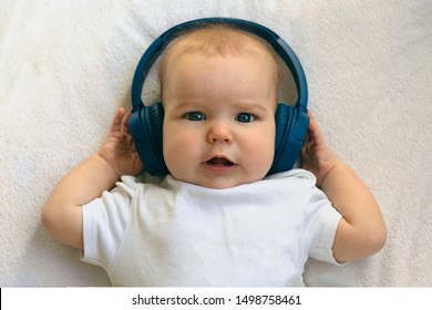 Baby child Toddler Happy smiling in wireless blue headphones on a white background. The concept of technology learning from birth and fine music. Boy listens to music and holds headphones in his hands