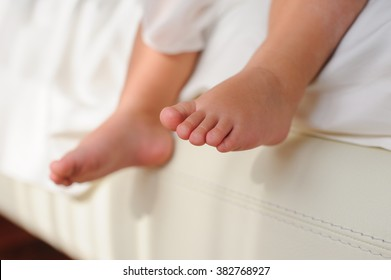 Baby or Children foot  sitting on the white bed, closeup.