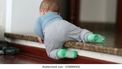 Baby climbing down step for first time. Toddler infant learning to climb down stair
