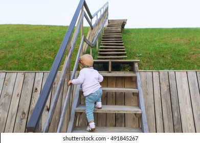 The baby climbs up a ladder into sky