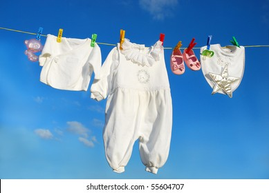 baby clothes and accessories hanging on clothesline against blue sky