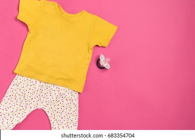 Baby clothes and accessories on pink background. Top view