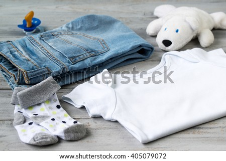 5ea6b962f Baby clothes and accessories with white bear toy on a wooden background