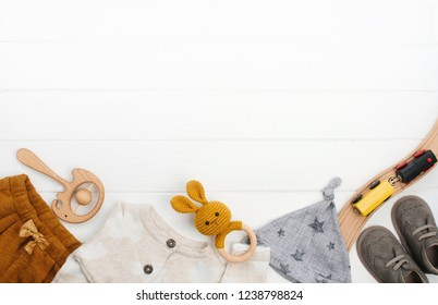 Baby clothes, booties and wooden toys on white wooden background with blank space for text. Top view, flat lay.
