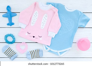 Baby clothes concept. Blue bodysuit for boy and pink shirt for girl near baby accessories on white wooden background top view