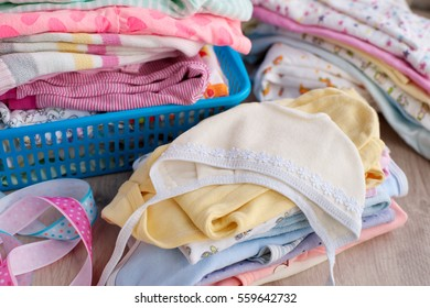 Baby clothes. Baby clothes folded by a stack. Sliders and brightly colored loose jackets. Clothing for children in a basket for clothes. The children's cap of white lace embroidery.