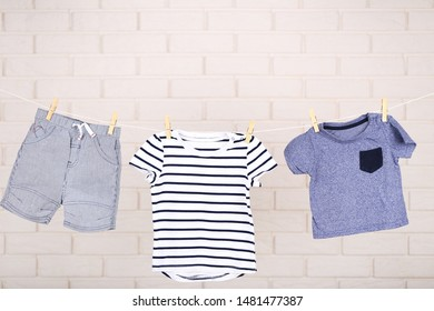 Baby clothes hanging on brick wall background