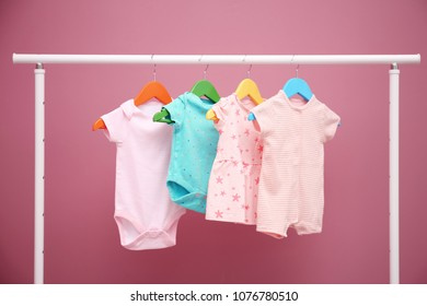 Baby clothes hanging on rack against color background