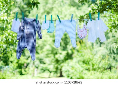 Baby clothes on clothesline drying in garden. Newborn childhood concept