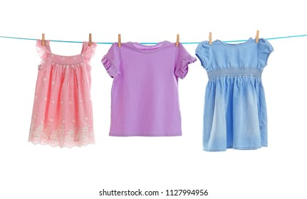Baby clothes on laundry line against white background