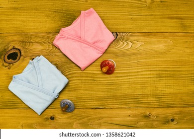 Baby clothes and pacifier for boy and girl  on wooden table.Baby announcement concept.Toned photo.