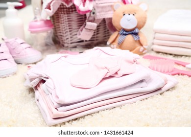 Baby clothes with soft bear toy on carpet