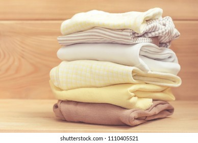 Baby clothes stack for newborn on wooden background. In pastel colors. concept natural organic textile