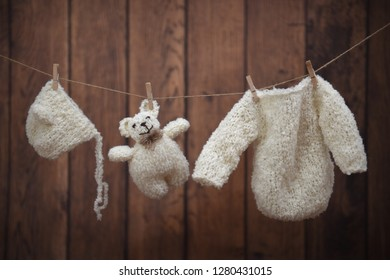 Baby clothes and teddy hanging on wooden background