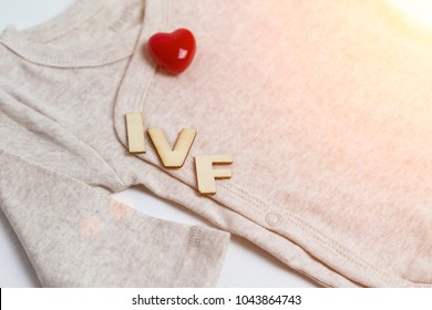 Baby clothes with test-tube and heart. Concept - IVF, in vitro fertilization. Waiting for baby, pregnant.