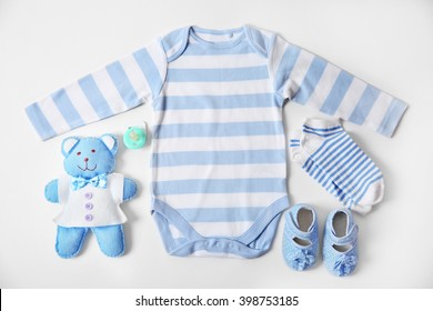 Baby clothes with toys on white background