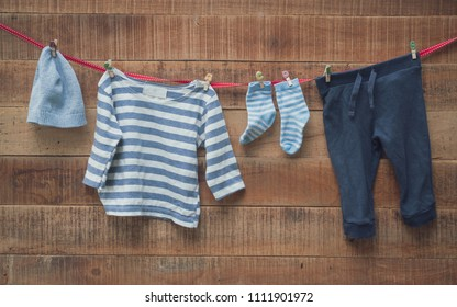 Baby clothes were drying at the clothesline and wooden backdrop
