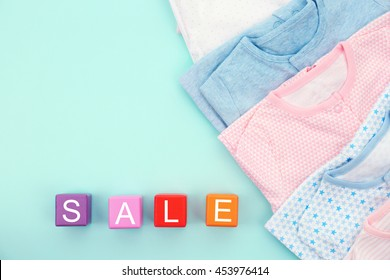 Baby clothes and wooden cubes on color background. Sale concept