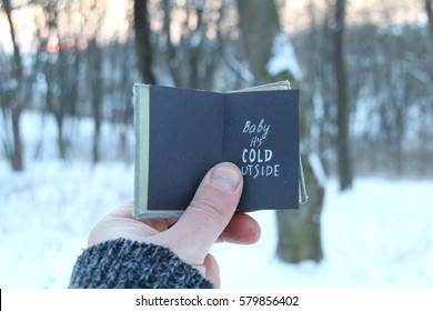 Baby its cold outside. Winter holiday lettering on the book.