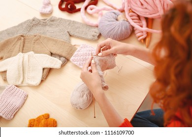 Baby collection. Professional skillful needlewoman feeling extremely inspired while working on knitted baby collection