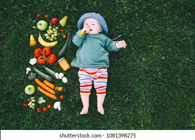 Baby in colorful clothes trying food and frame of different fresh fruits and vegetables on green grass background, top view. Healthy child nutrition, baby feeding.