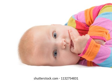 baby in colorful longsleeve holds a finger in mouth