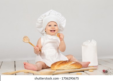 Baby cook. Beautiful little girl in cook clothes with a long loaf and a wooden spoon. The child is one year old. Funny baby.