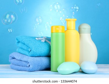 Baby cosmetics, towels and soap on wooden table, on blue background