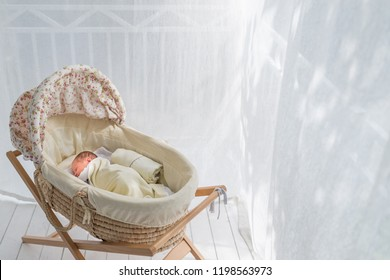 Baby cradle on balcony with white curtain