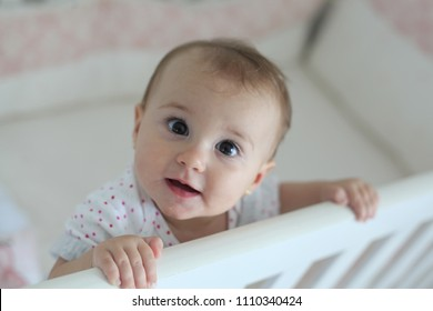 baby in crib looking towards camera, baby holding on the edge of the crib,  baby with happy look.