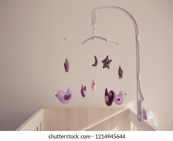 Baby crib Mobile with Stuffed Birds. Purple, violet and pink handmade birds in the nursery. Concept of newborn, softness, child and love.