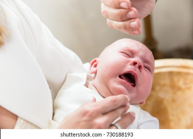 Baby is crying at christening while the priest pours holy water over its head
