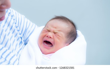 Baby crying,Crying innocent baby,Asian cute baby girl hugging her mother crying,Portrait of a loving mother holding baby and talking to calm,Newborn baby girl crying portrait,Body language is natural,