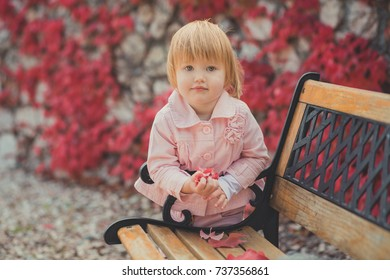 Baby cute girl with blond hair and pink apple cheek enjoying spring autumn time holiday posing in beautiful garden full of flowers on bench wearing pinky shirt dress pens.
