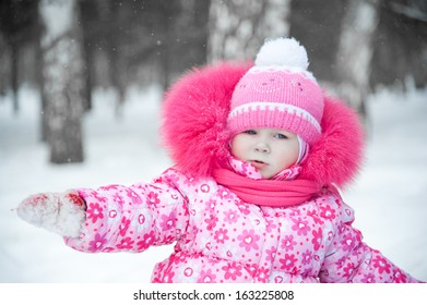Baby cute girl riding on a snowy hill in winter
