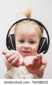 baby, cute girl in wireless headphones listening to music