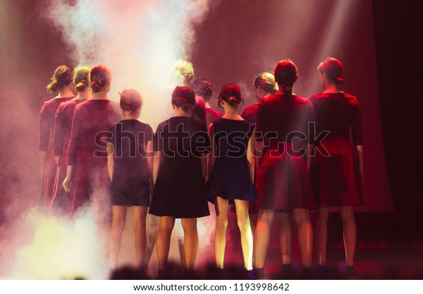 Baby dancing game . The scene in the rays of colored spotlights . Synchronous movement . The young talents. Colored lamps , red color
