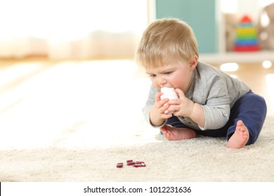 Awesome Baby In Danger Playing With A Bottle Of Medicines On The Floor At Home