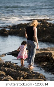 Baby daughter walking on the rocky beach with her mother.