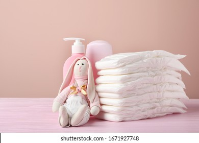 Baby diapers, toy bunny and toiletries on wooden table against pink background