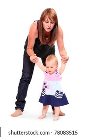 Baby doing her first steps with mother help. Studio shot on white background.