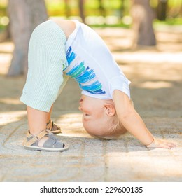 Baby doing yoga exercises. Downward Facing Dog pose. Adho Mukha Svanasana